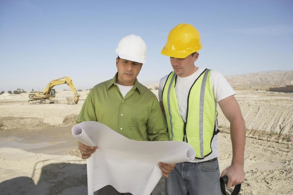 Two men looking at plans for a new concrete building in Delaware County Pa