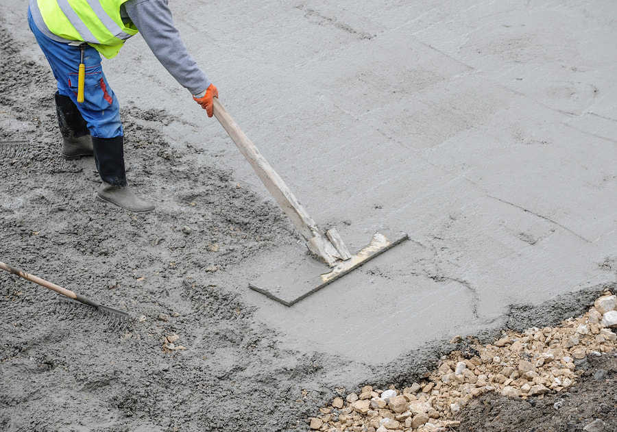 A Picture Of A Worker Smoothing Out Concrete With A Home Made Wood Float. Delaware County Concrete Services