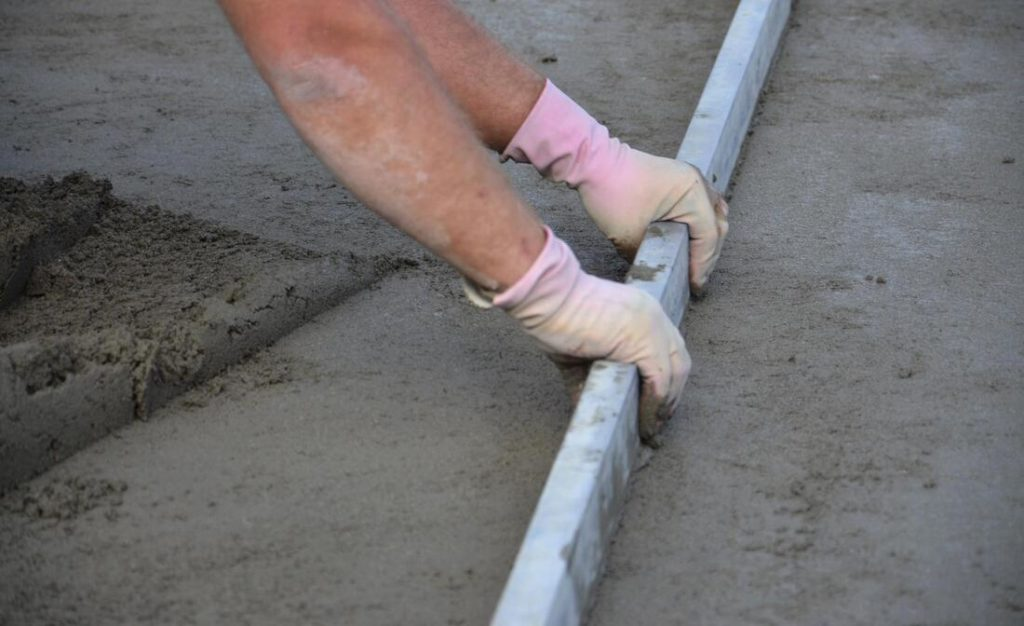A Picture Of A Concrete Worker Smoothing Out Concrete Before Troweling It out With A Metal Screed. Concrete Contractors In Delaware County Pa