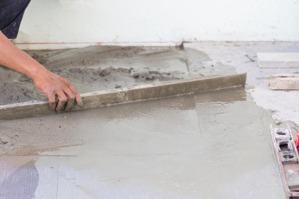 A Picture Of A Delaware County Concrete Contractor Working The Concrete Down With A Board To Level It Out Before Smoothing It Out Concrete Contractors In Delaware County Pa