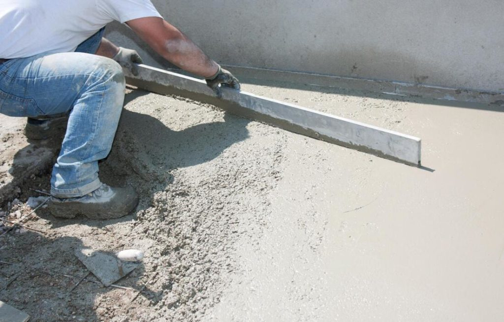 A Picture Of A Concrete Worker Using A Long Board To Flatten Concrete So It Can Be Worked Smooth By Concrete Contractors In Delaware County pa