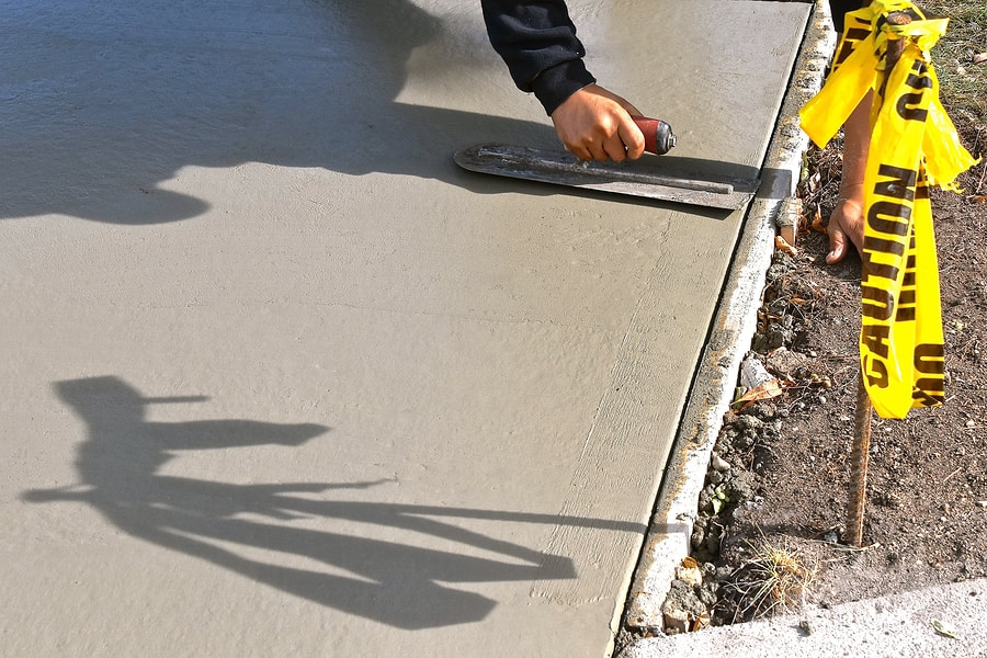 A Picture Of A Concrete Worker Smoothing Out Concrete After Letting It Set Up For Concrete Contractors In Delaware County Pa